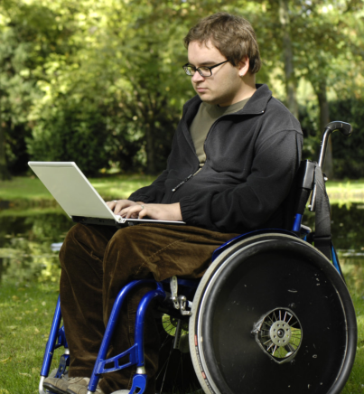 guy in a wheelchair using a laptop